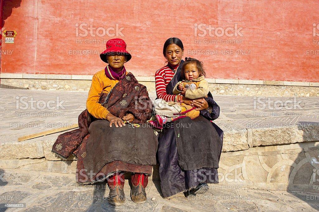 Tibetan women and children sitting outside temple stock photo