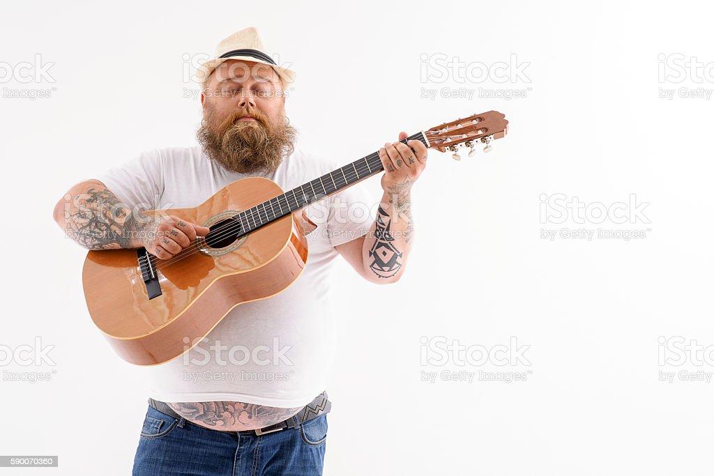 Tick male guitarist creating music stock photo