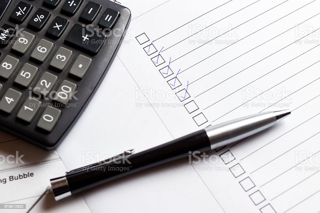 Ticked boxes on check list with pen and calculator. stock photo