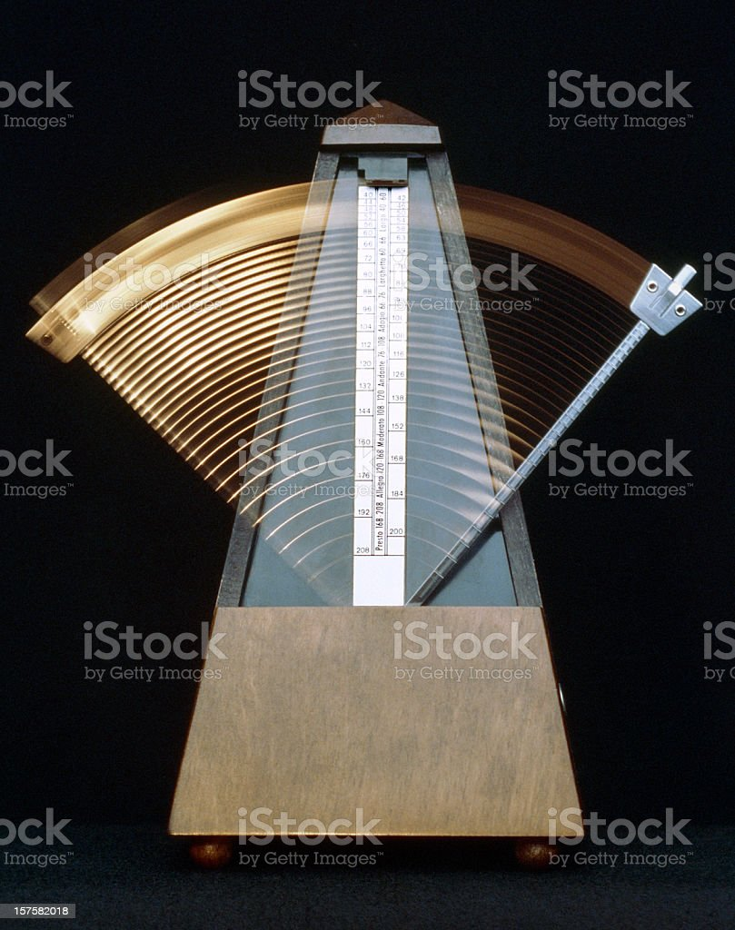 Ticking metronome in motion on a black background stock photo
