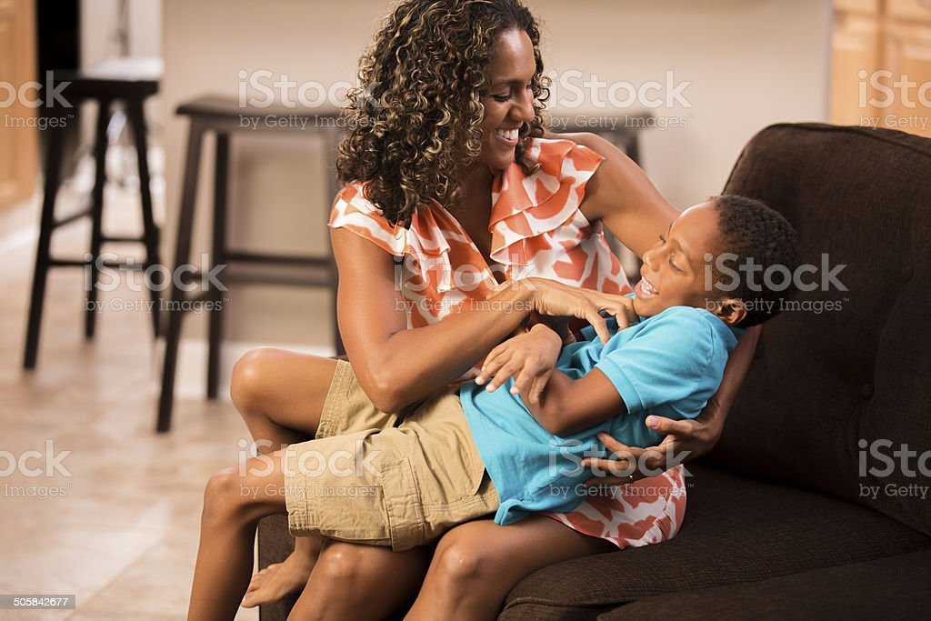 Tickle me! Laughing little boy tickled by his mother. Home. stock photo