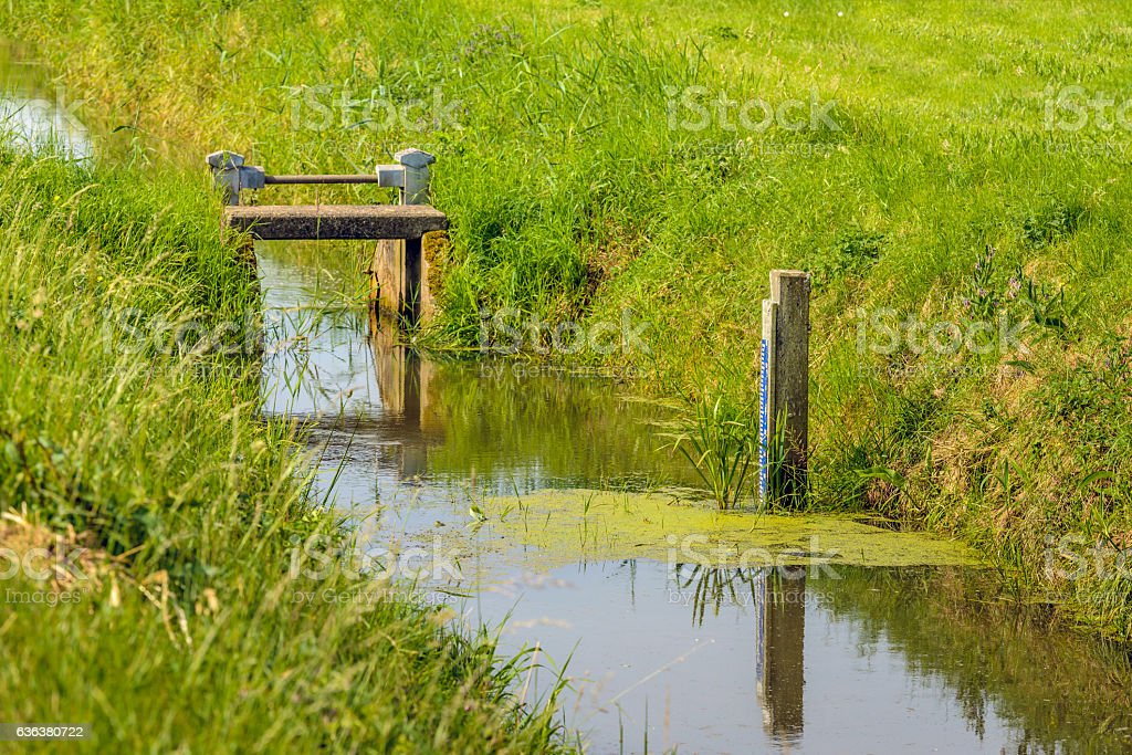 Tide gauge and small weir in a ditch stock photo