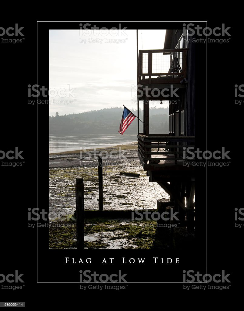 Tide out and American flag on condo over the bay stock photo