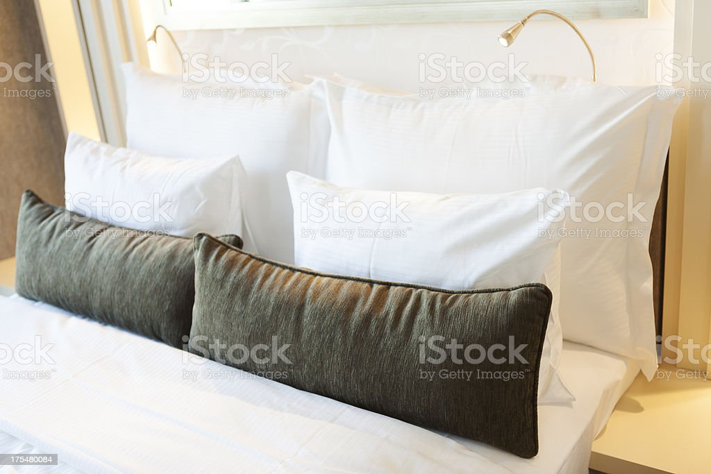 Tidy hotel bed with pillows and bedside lamps royalty-free stock photo
