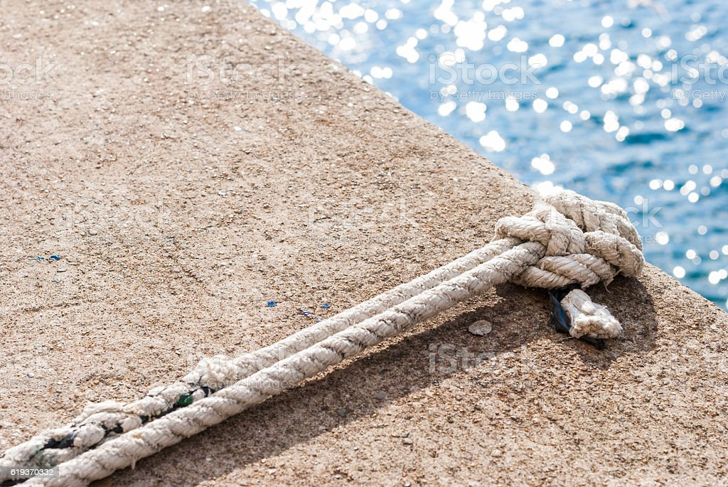 Tied knot on dock with blue sea on background stock photo