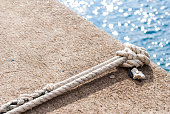 Tied knot on dock with blue sea on background