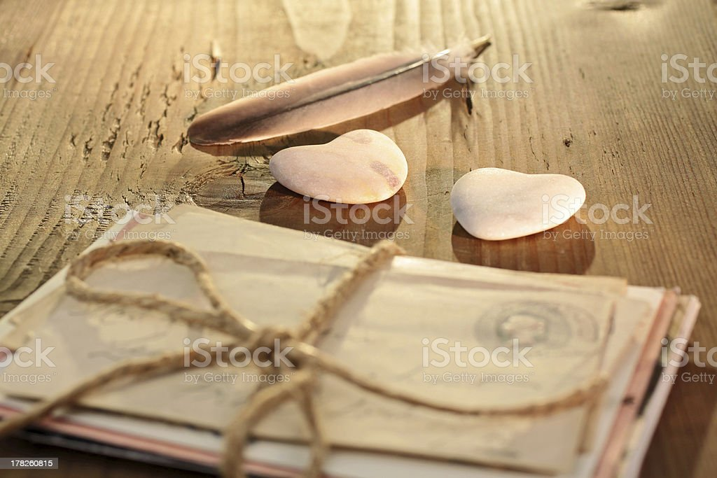 Tied letter with stone hearts and a feather stock photo