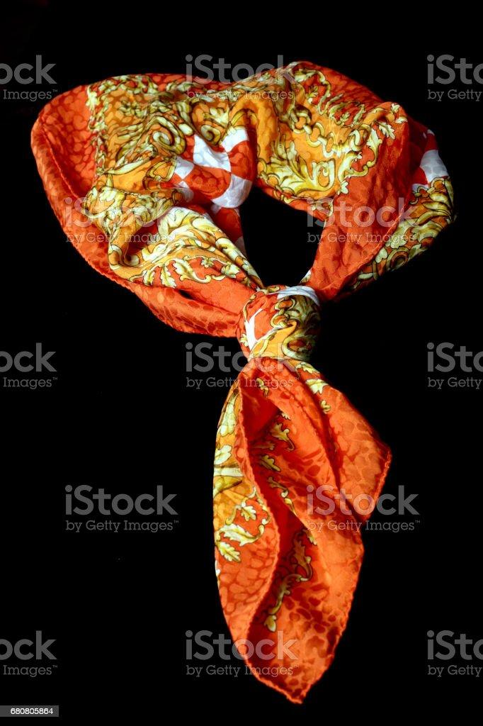 Tied silk scarf on black backdrop stock photo