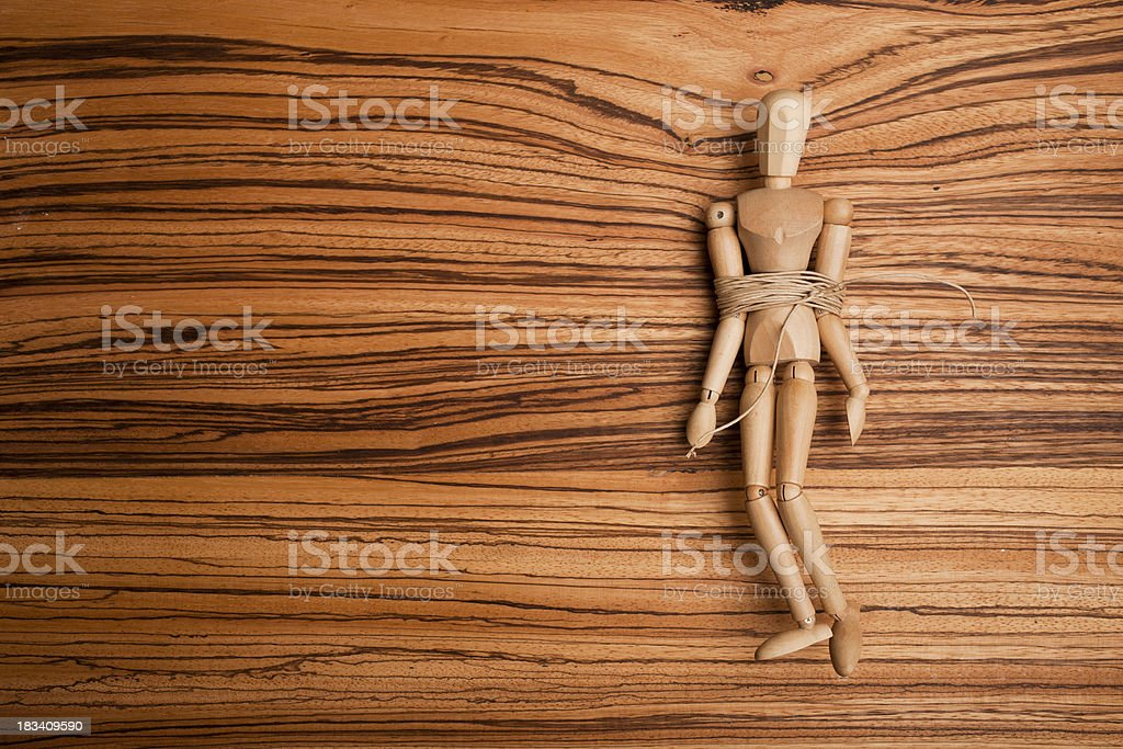 tied wooden figurine on a wood brown table stock photo