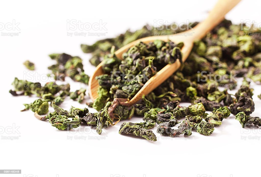 Tieguanyin chinese Oolong tea in a wooden scoop stock photo