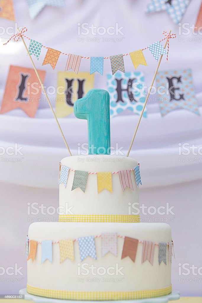 Tiered birthday cake decorated with colorful buntings stock photo