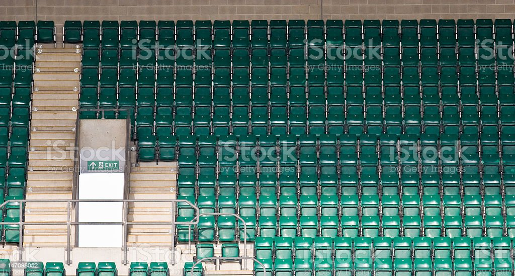 Tiered Green Seats Sit Empty in a Large Sports Stadium stock photo