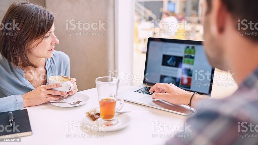 Tight shot of woman looking at laptop over mans shoulder stock photo