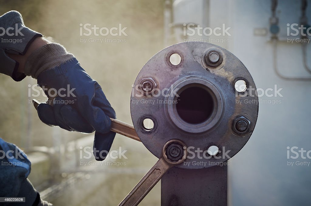 Tightening nut and screw on pump station. stock photo