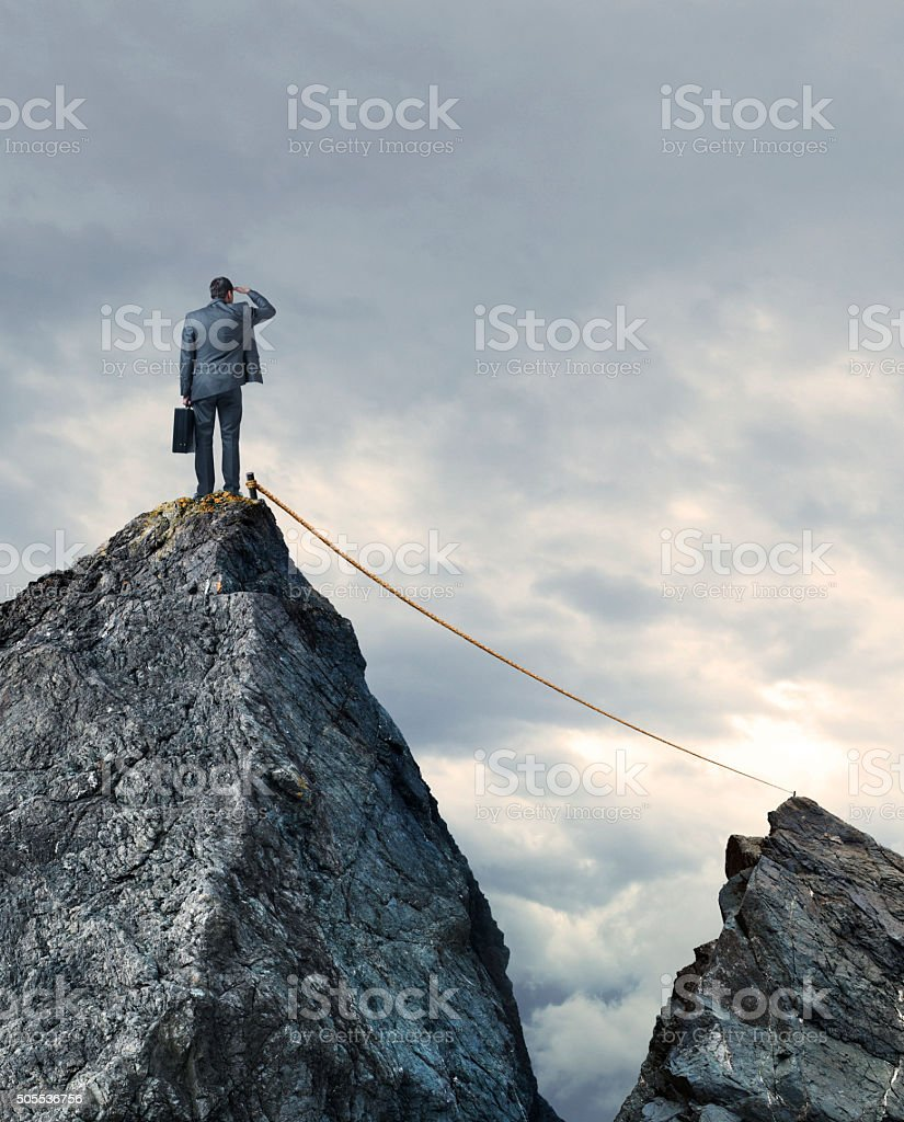 Tightrope Connecting Two Mountain Tops As Bunessman Looks On stock photo