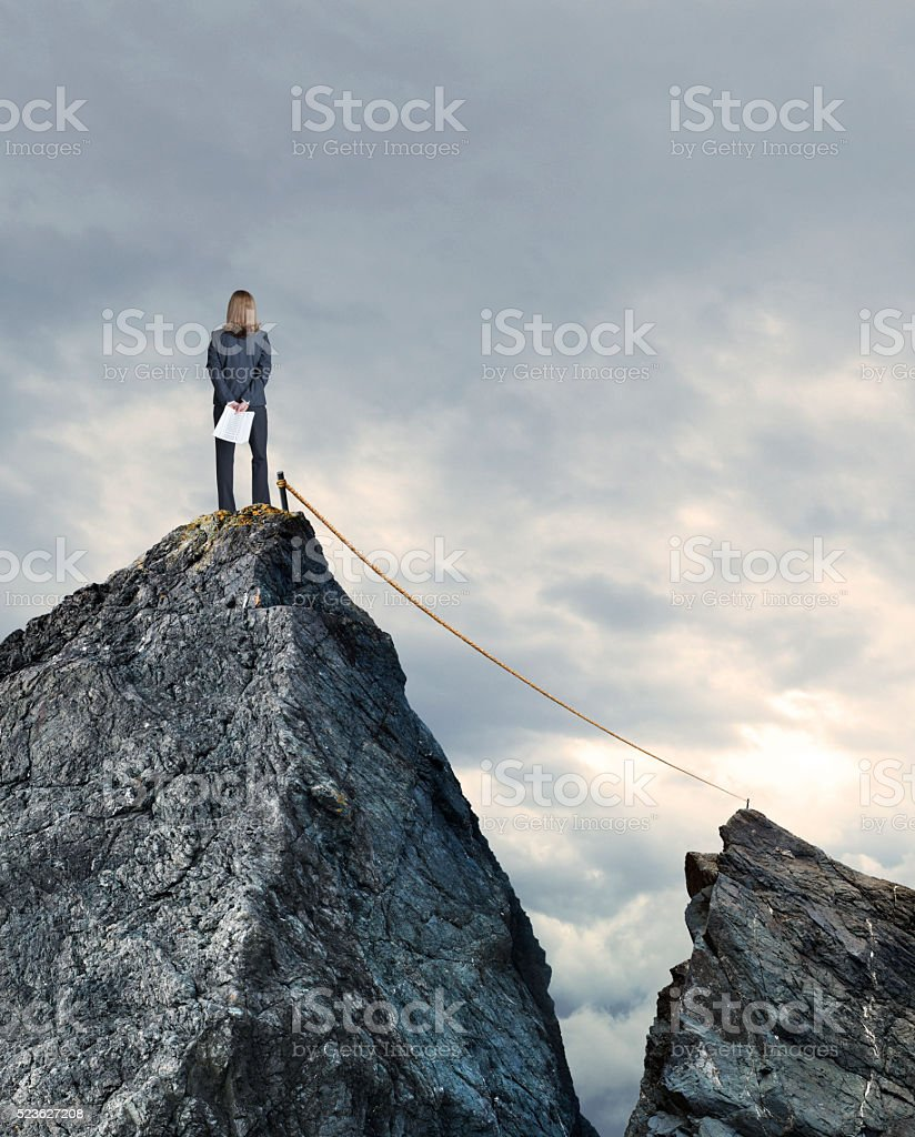 Tightrope Connecting Two Mountain Tops As Bunesswoman Looks On stock photo