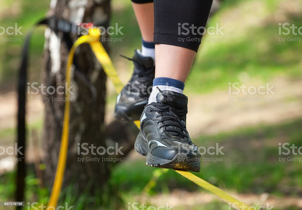 Tightrope walker is on a tight sling. stock photo