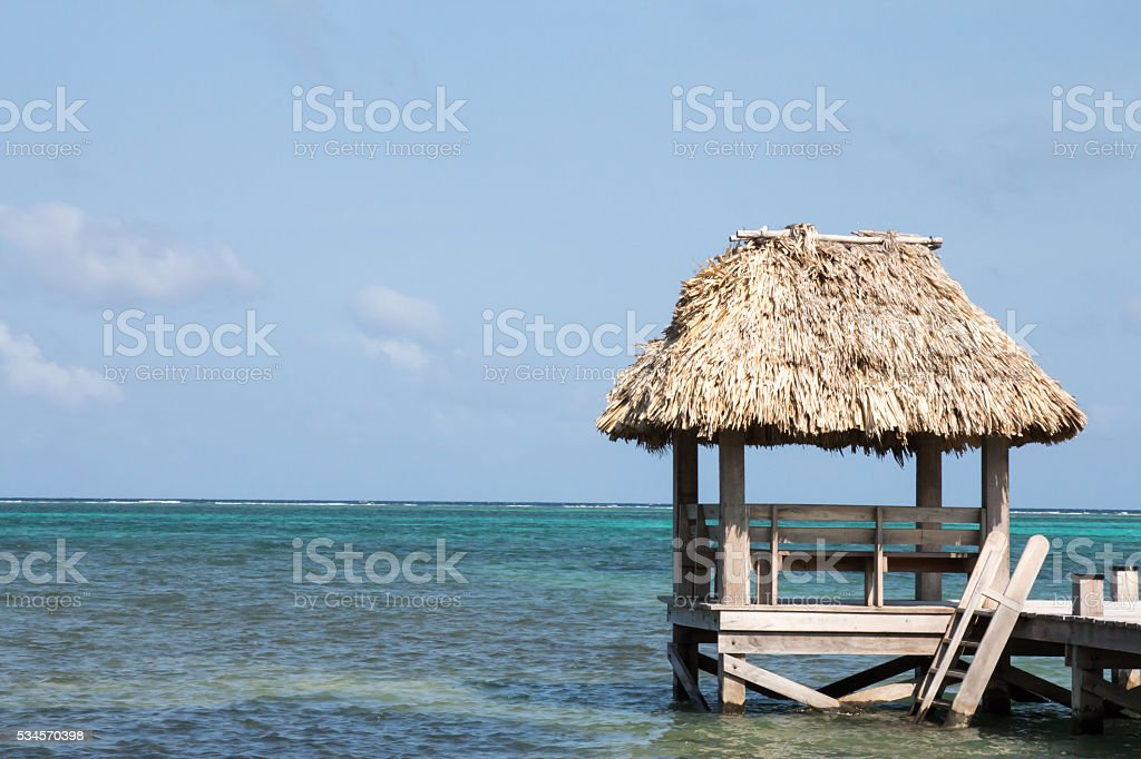 Tiki hut shade roof on pier in Belize stock photo