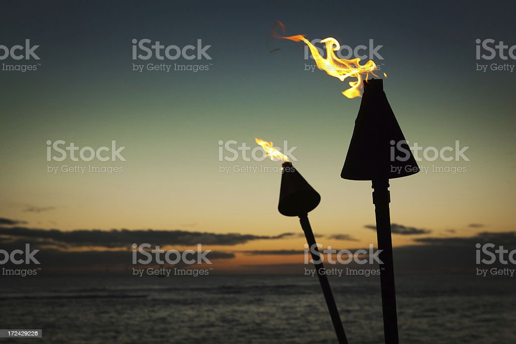 Tiki Lamps in Tropical Beach Sunset Hz stock photo