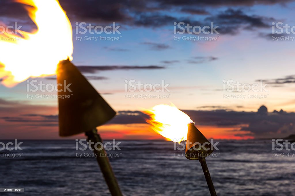 Tiki Torch Flames on Tropical Beach at Sunset stock photo
