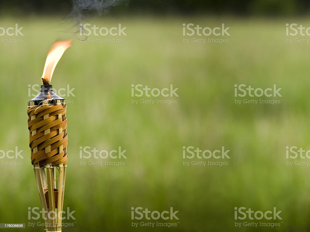 Tiki Torch with Blurred Grass Background stock photo