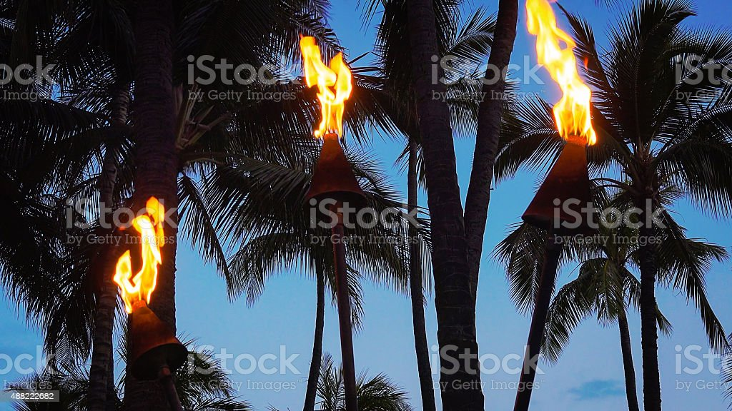 Tiki Torches Burning on Waikiki Beach at Night stock photo