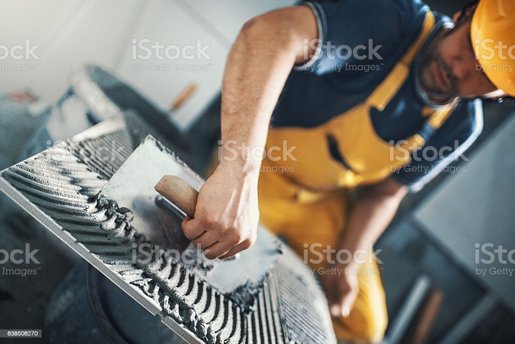 Tile handyman applying adhesive on a tile. stock photo