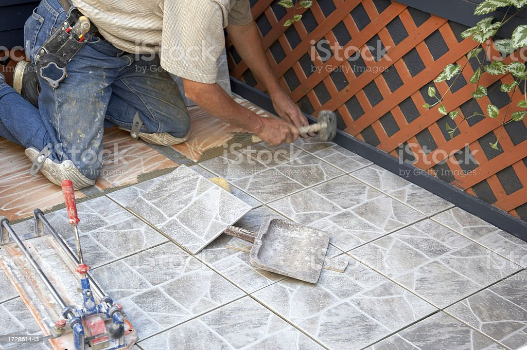 Tile layer at work using hammer stock photo