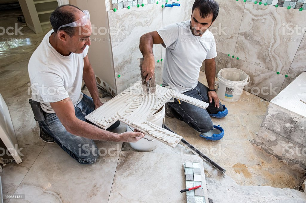 Tile series: New tile being installed in shower of home stock photo