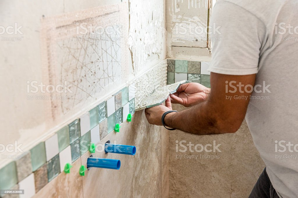 Tile series:Tile border being installed on shower wall in home stock photo