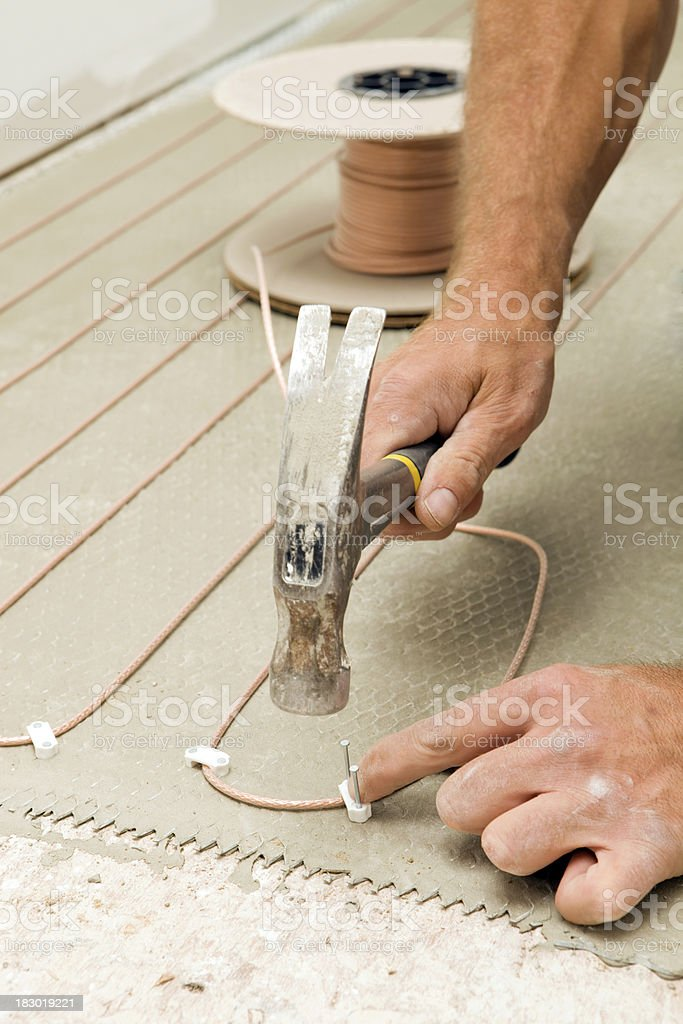 Tile Setter Installing Electric Radiant Floor Heat in a Bathroom stock photo
