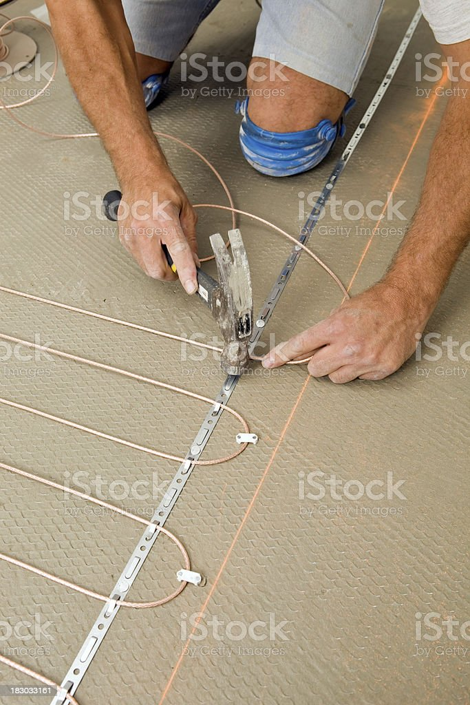 Tile Setter Installing Electric Radiant Floor Heat in a Bathroom royalty-free stock photo