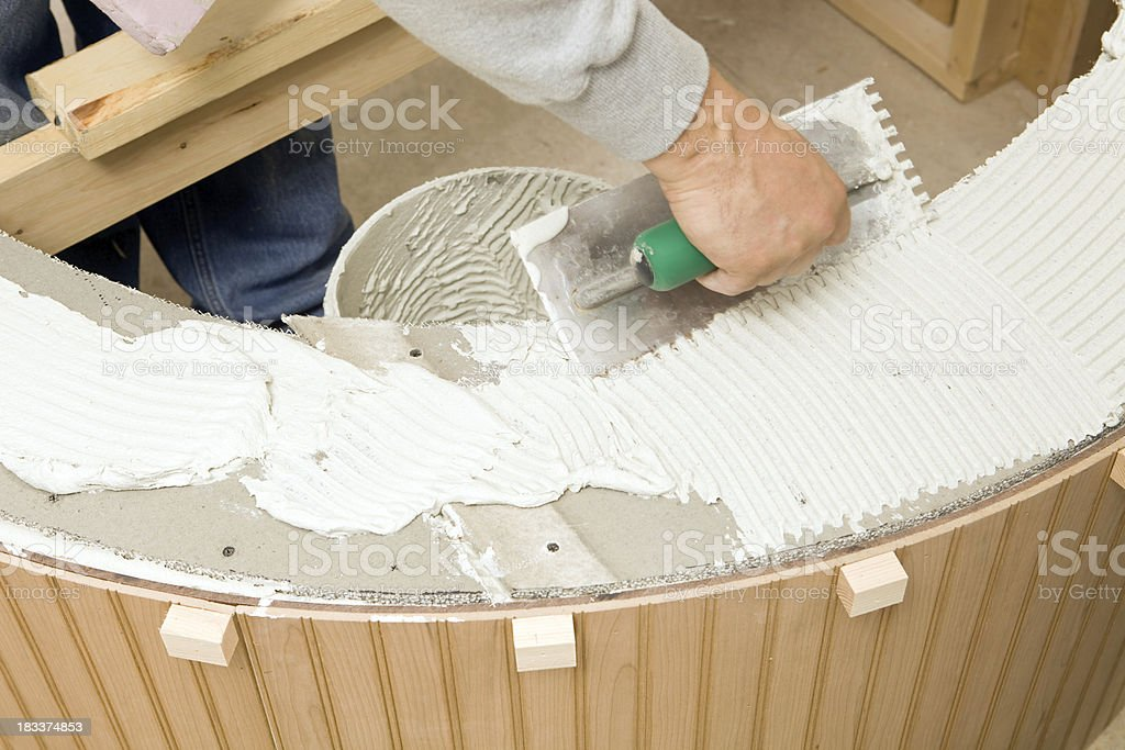 Tile Setter Spreading Mortar for a Marble Bathtub Surround royalty-free stock photo