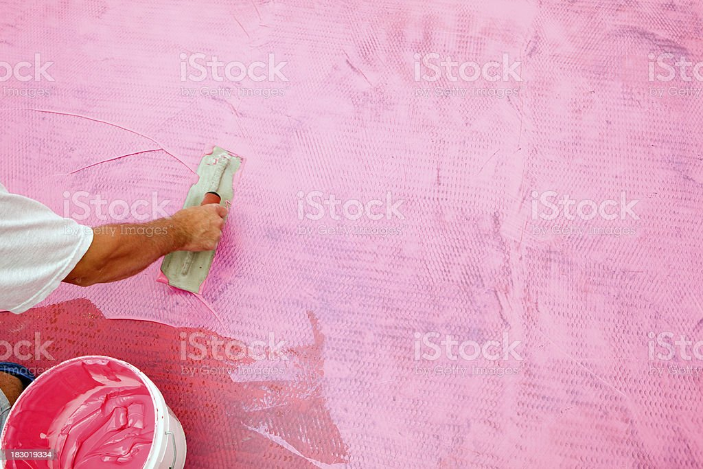 Tile Setter Spreading Waterproof Membrane on Laundry Room Floor royalty-free stock photo