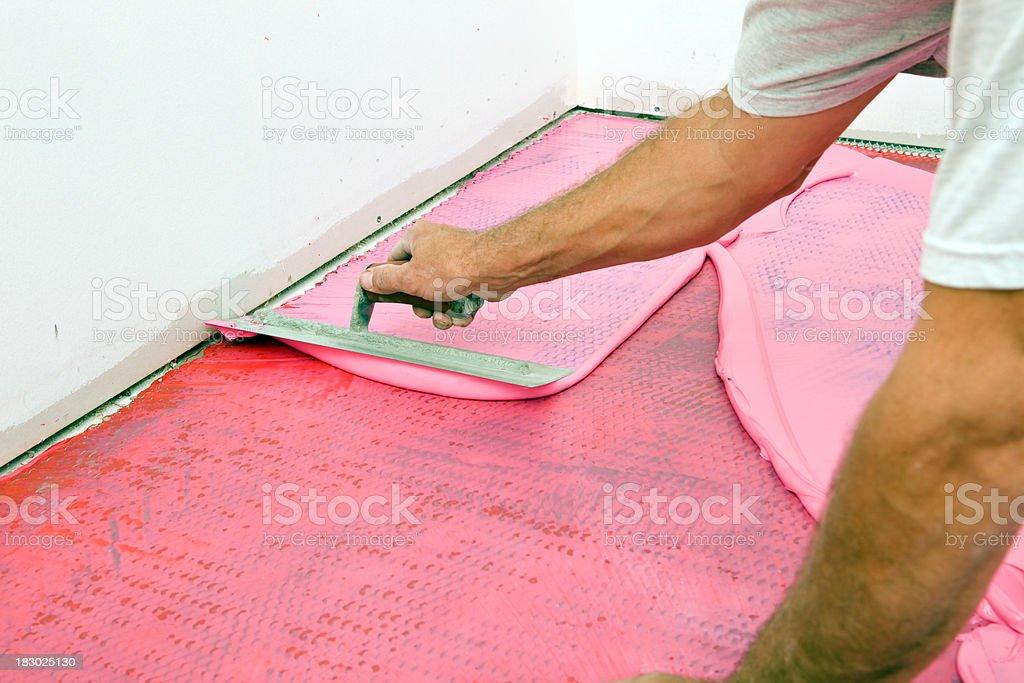 Tile Setter Spreading Waterproof Membrane on Laundry Room Floor stock photo