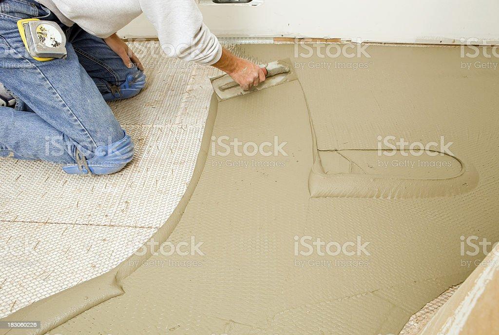 Tile Setter Troweling Mortar on Mesh Subfloor stock photo