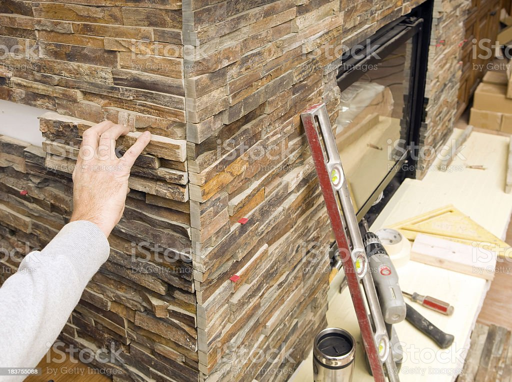 Stacked Stone Fireplace Surround tile worker placing stacked stone piece for a fireplace surround