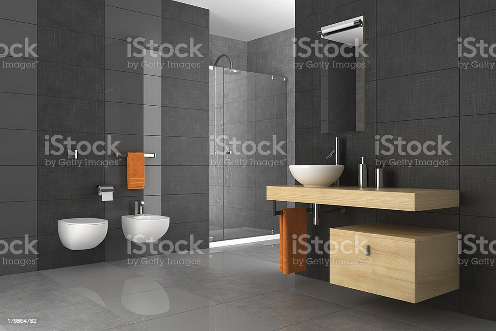 A tiled bathroom with a wood counter and orange towels stock photo