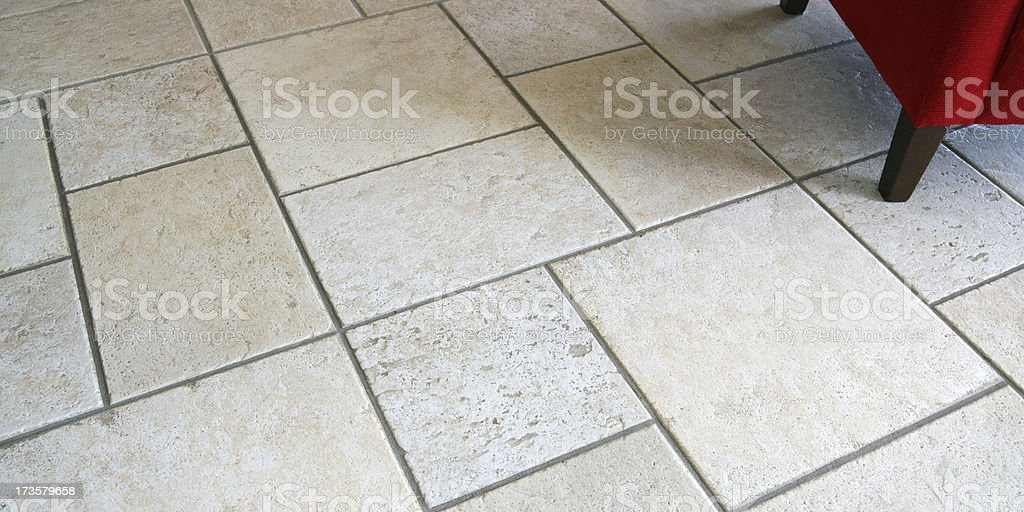 Tiled floor, Italian ceramic tiles with red chair in corner royalty-free stock photo