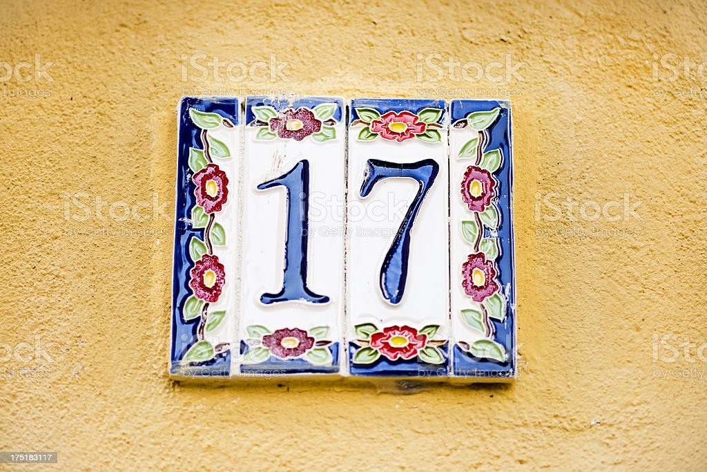 Tiled number 17 on yellow wall stock photo