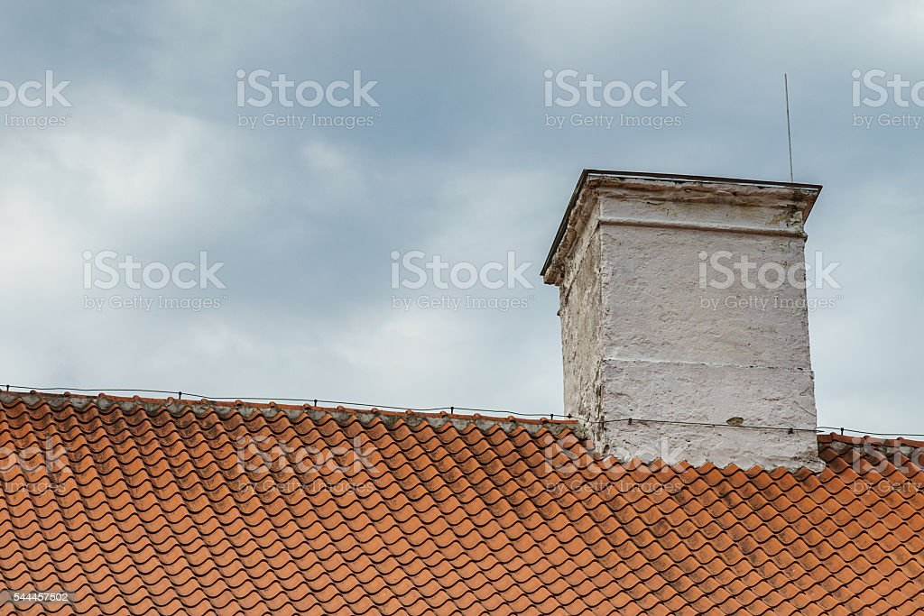 Tiled roof and chimney with lightning rod stock photo