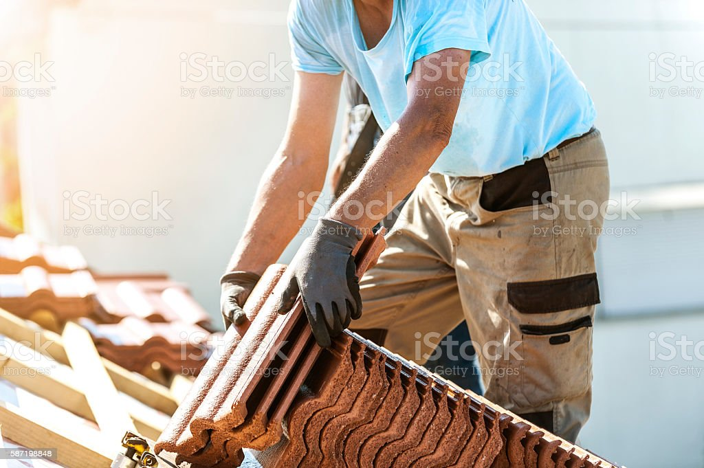 Tiler covering roof with new tile stock photo