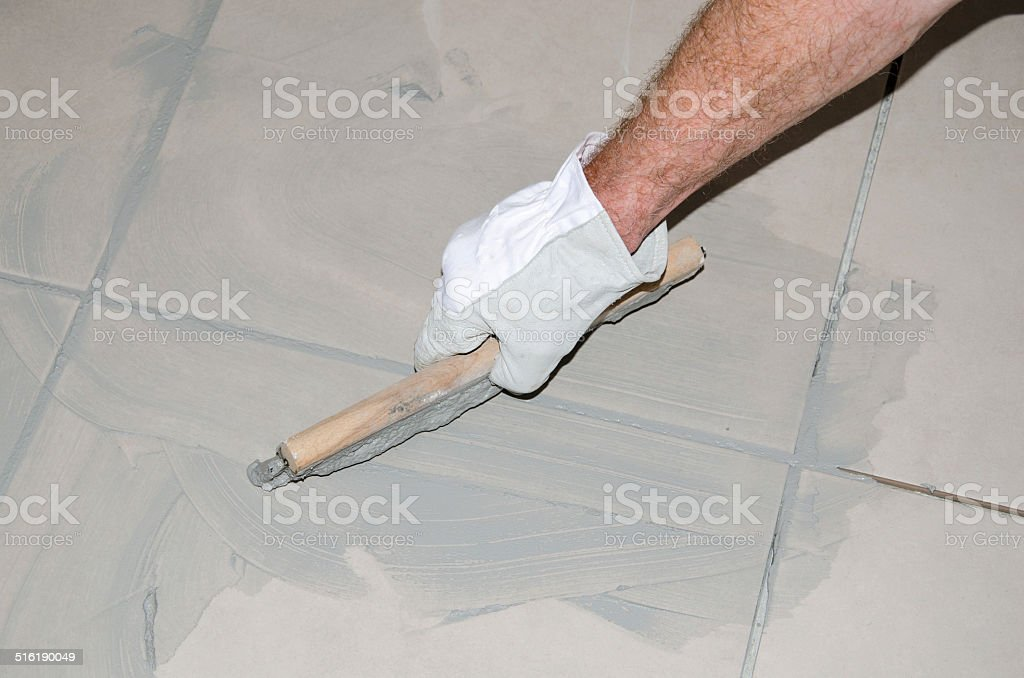 Tiler filling up joints with a rubber squeegee stock photo