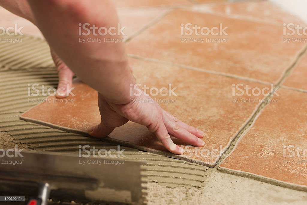 Tiler fitting terra cotta tiles on a floor royalty-free stock photo