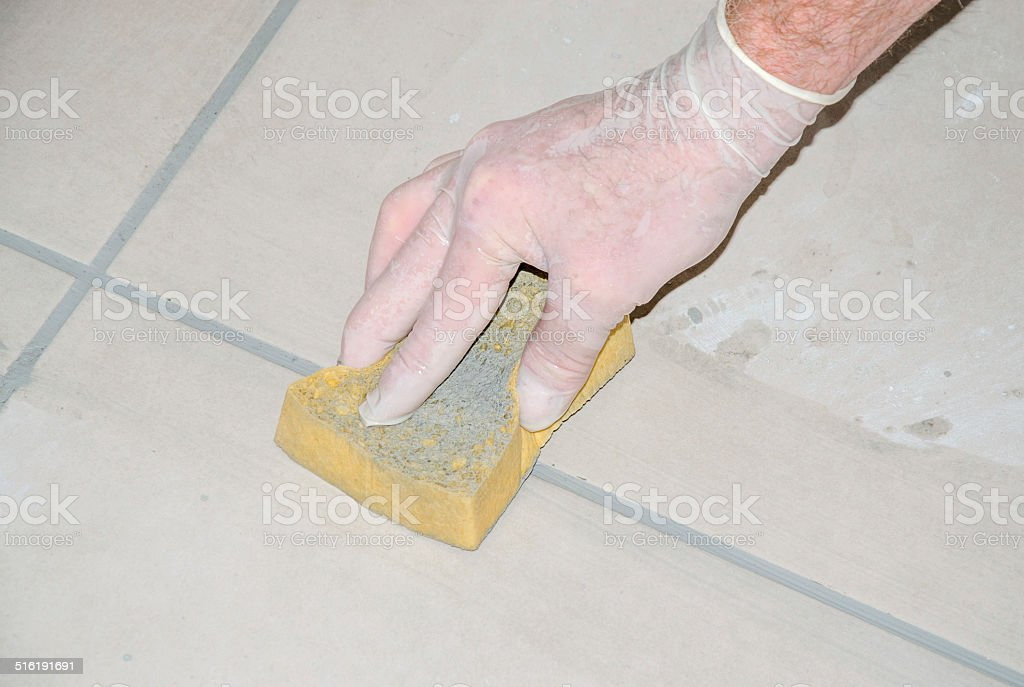 Tiler smoothing tile joints with a sponge stock photo