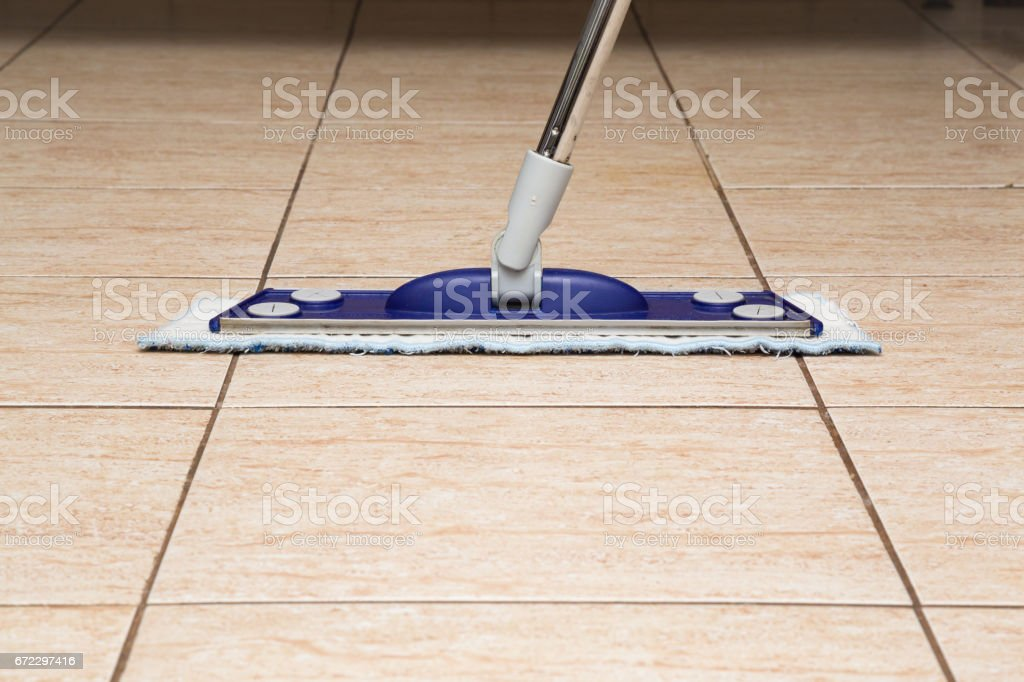 Tiles floor washing with mop in the kitchen. Regular clean up. Maid...