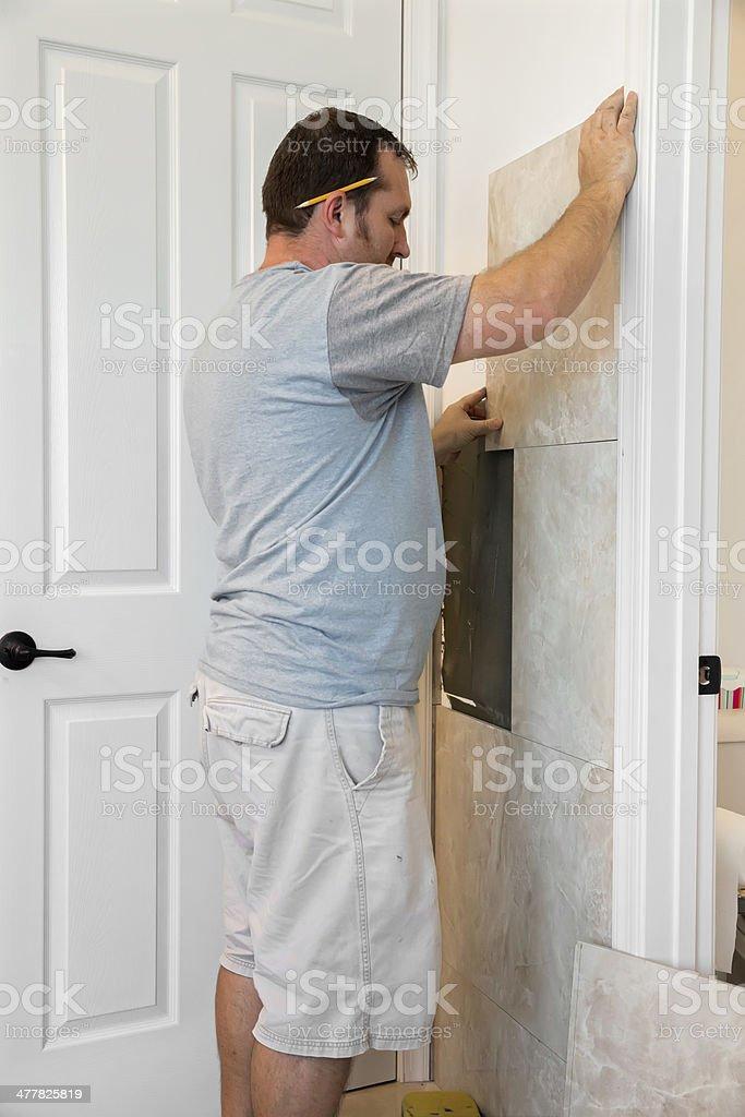 Tiling a bathroom wall royalty-free stock photo