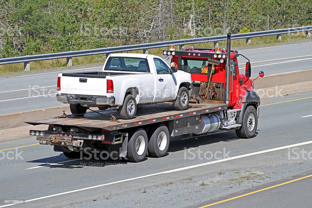 Tilt Bed Tow Truck Transporting An Old Model, Nondescript Vehicle stock photo