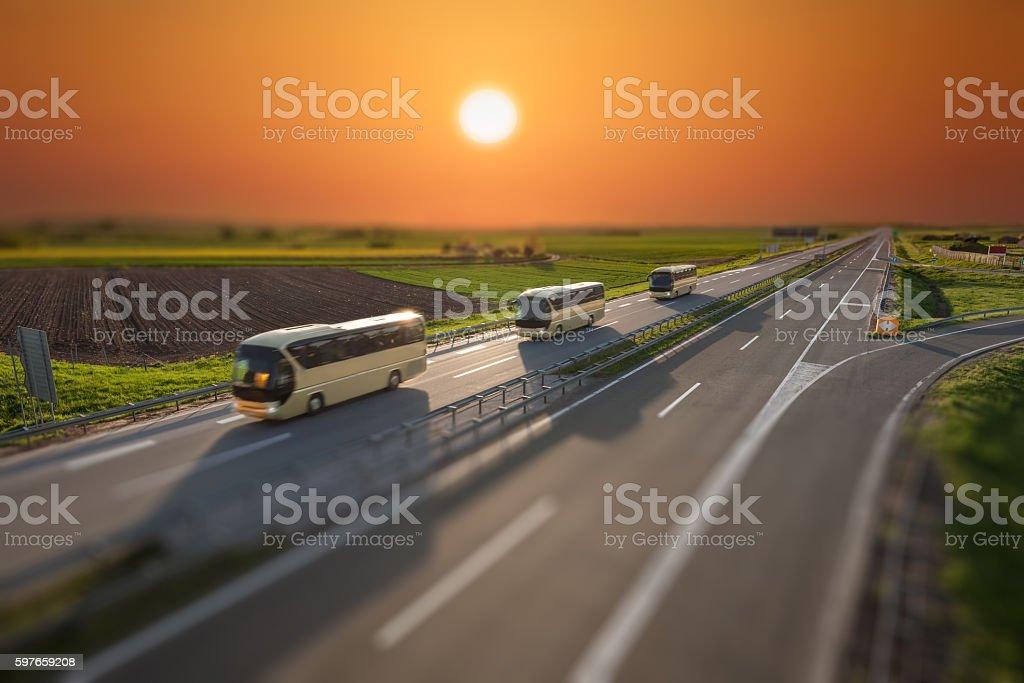 Tilt shift image of travel buses on highway at sunset stock photo