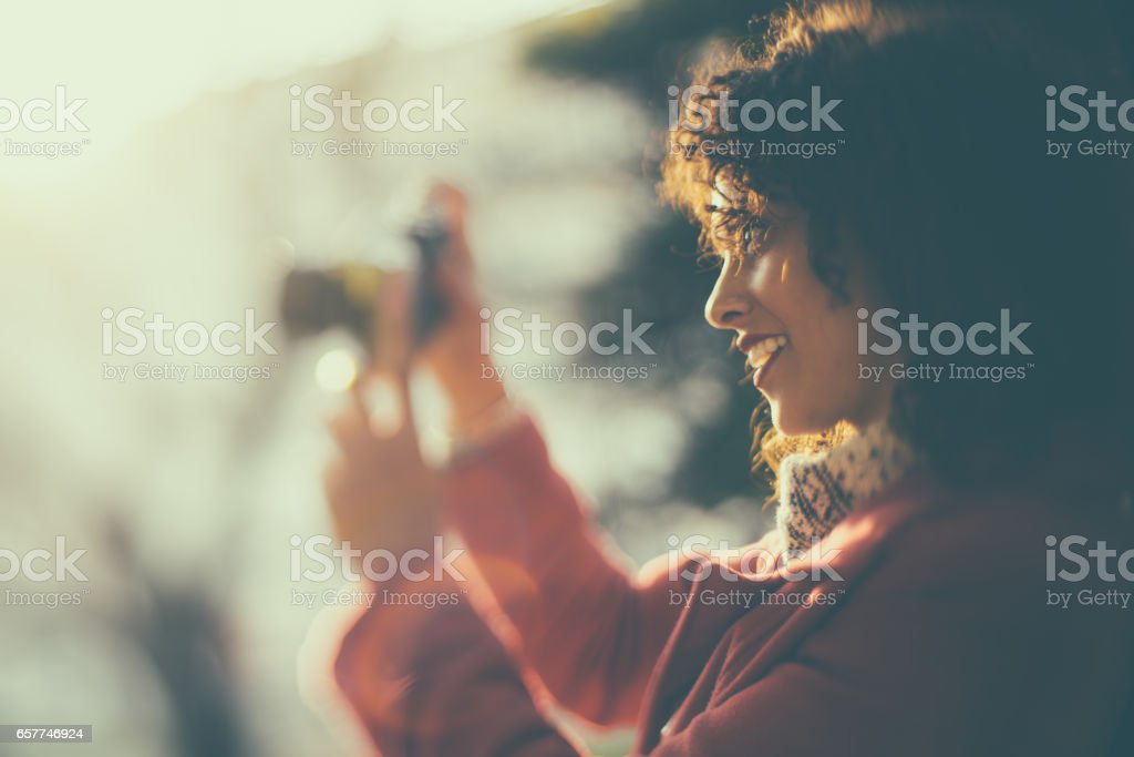Tilt shift portrait of curly woman with photo camera stock photo